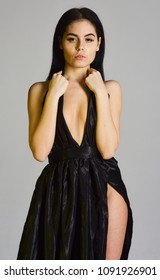 Sexy decollete concept. Woman in elegant black evening dress with decollete, grey background. Attractive girl wears expensive fashionable evening dress with erotic slit. Lady, sexy girl in dress