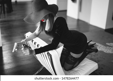 Sexy dominant femme fatale in hat holding whip on sofa, kneeling and looking down, black and white and red lips, selective coloring