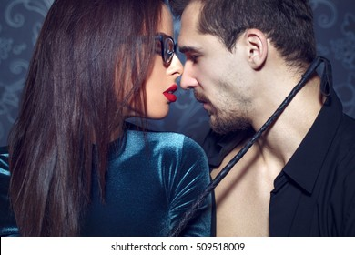 Sexy dominant milf woman in glasses, red lips, holding whip to young lover, sensuality, bdsm