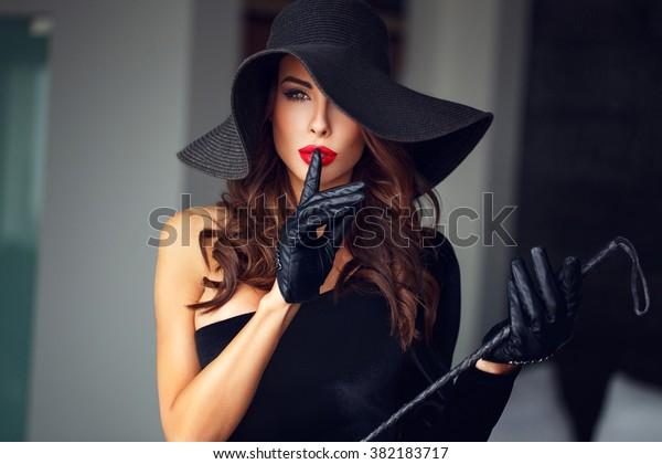 色っぽい女性が帽子とむちを着て、話をしないbdsm