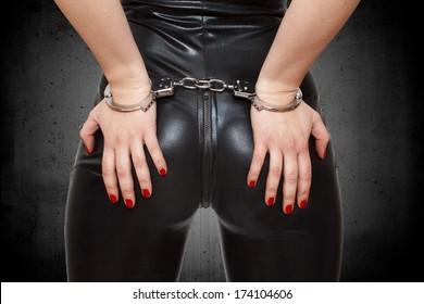 Sexy dominatrix, hands in handcuffs, closeup