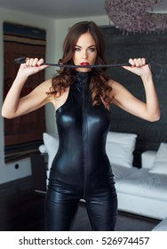 Sexy dominatrix holding whip in latex catsuit