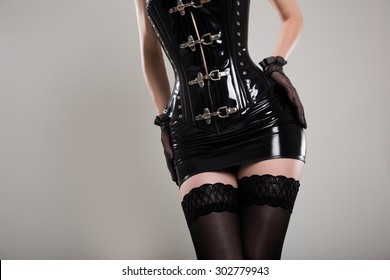 Sexy dominatrix woman in black latex corset with spikes, skirt and stockings