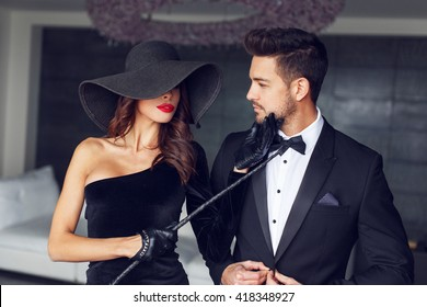 Sexy dominatrix woman posing with whip and young macho lover in tuxedo