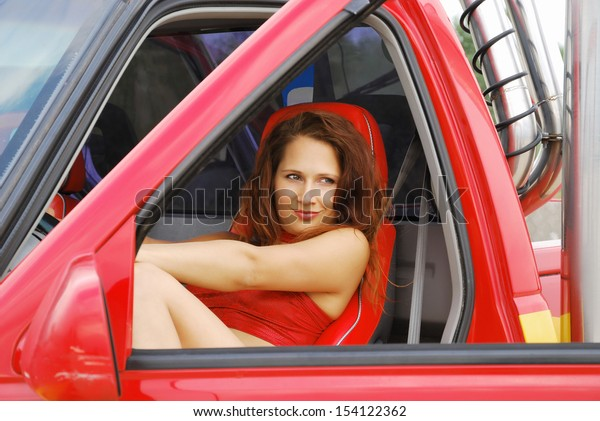 A sexy driver is resting in the red off-road vehicle. The photo is made through the window of front door opened. Young woman is wearing red strapless top and shorts.