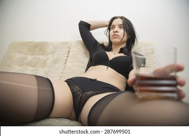 Sexy Drunk girl with glass of alcohol on the sofa at home