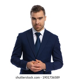 sexy elegant guy in navy blue suit smiling, touching fingers and posing, standing isolated on white background in studio, portrait