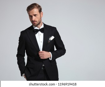sexy elegant man wearing tuxedo and bowtie posing on grey background