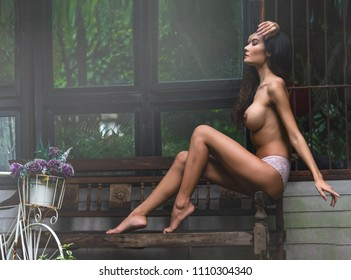 Sexy elegant topless women with lace pantie sitting on antique wooden bench with bicycle on left side.