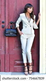 Sexy elegant woman natural beauty fashion style clothes casual white suit white cotton blazer and pants,black bag and high heels Sophisticated self-confident brunette standing in front of retro door