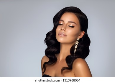 Sexy elegant young woman with Hollywood wave of hair. Portrait Attractive charming girl with big curls. Salon smooth hair. Jewelry shiny decoration