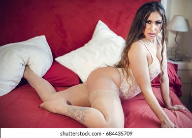 Sexy erotic lingerie fashion model woman on bed being sensual