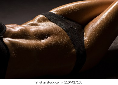 Sexy and erotic woman body parts, closeup about a slim, muscular belly and legs, with black lingerie