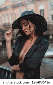 Sexy erotic woman in hat and cloak naked outdoors at city streets