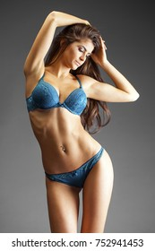 Sexy fashion brunette woman with long dark hair in blue lingerie, isolated on dark gray background