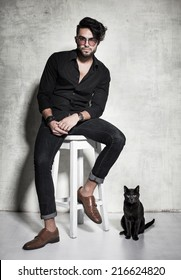sexy fashion man model dressed casual posing with a cat against grunge wall