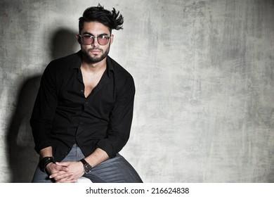 sexy fashion man model dressed casual posing dramatic against grunge wall