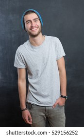 sexy fashion man or student dressed casual smiling against chalkboard