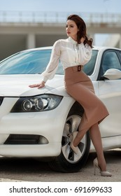 Sexy fashion woman in elegant summer clothes posing at sport car. Vogue outdoor portrait of sensual brunette model near car.