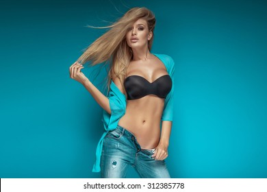 Sexy fashionable blonde woman posing on blue background, wearing black bra and jeans. Girl with perfect slim body. Studio shot.
