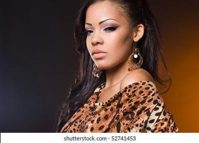 Sexy fashionable mulatto woman on orange