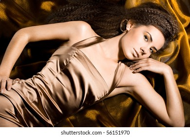 Sexy fashionable woman in golden dress