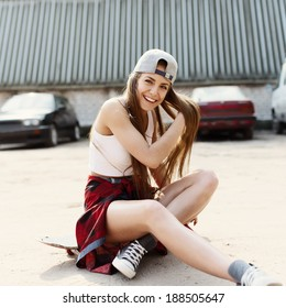 Sexy fashionable woman sitting on a skateboard laughs