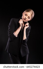 Sexy fashionable woman in suit on black background in studio photo. Glamour and elegance