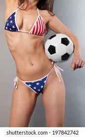 sexy female in american bikini holding a soccer ball