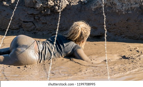 Sexy female athlete crawling under barbed wire at an obstacle course race