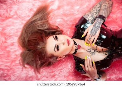 sexy female bdsm mistress in latex bodysuit in tattoo poses in sex poses on pink background