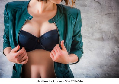 Sexy female breast. Attractive woman's body in black bra and leather jacket. Hot woman wearing unfastened leather jacket with black lingerie underneath