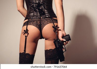 sexy female buttocks of young woman or girl in erotic panties and leather corset with a pistol in hand