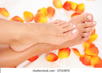 sexy female feet with rose petals on white duvet - beauty treatment