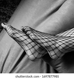 Sexy female feet, woman legs wearing fishnet stockings. Monochrome