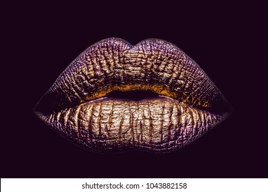 sexy female golden or gold lips isolated on black background as makeup or body art painted mouth metallized color with violet shade