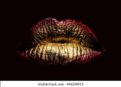 sexy female golden or gold lips isolated on black background as makeup or body art painted mouth metallized color with red contour