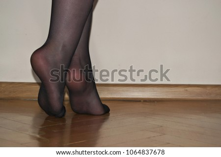 aaf6ae1589f Sexy female legs barefoot in black tights on a wooden floor. The woman is  standing