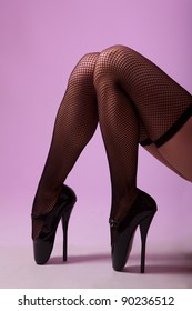 Sexy female legs in black fishnet stockings and fetish ballet shoes, studio shot