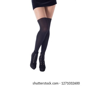 Sexy female legs in black gaiters and ankle high heels. Isolated on white, close up. Fall fashion and hosiery concept