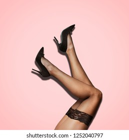 Sexy female legs in fishnet stockings and luxury high heel over pastel studio background. Fashion seductive pantyhose and black woman shoes.