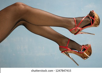 Sexy female legs in high heel black shoes and fishnet stockings on blue background.