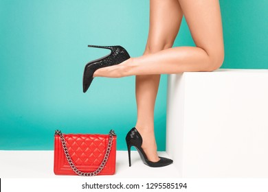 Sexy female legs in high heels with red handbag on a blue background. - Image