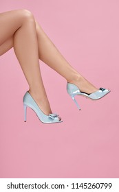 sexy female legs wearing blue high heels on pink background. summer time