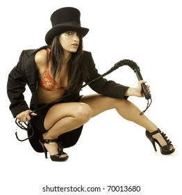 Sexy female lion tamer in circus top hat crouching