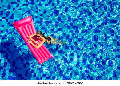 Sexy female model have a rest and sunbath on a float in the pool, top view aerial shot.woman in a black bikini swimsuit floating on an inflatable pink mattress spf and sunscreen top view