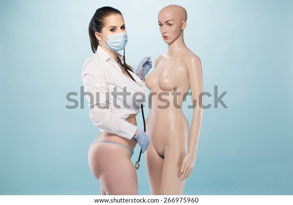 Sexy Female Nurse Wearing White Long Sleeves Shirt and Underwear with Mask, Gloves and Stethoscope Standing Besides a Human Dummy on a Very Light Blue Background.
