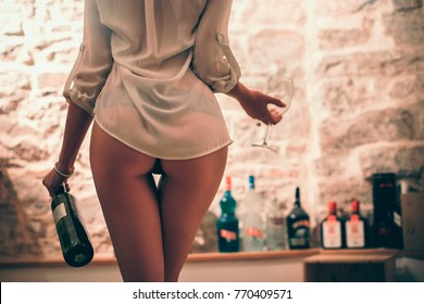 Sexy female in panties with bottle of wine and glass, female with sexy ass drinking