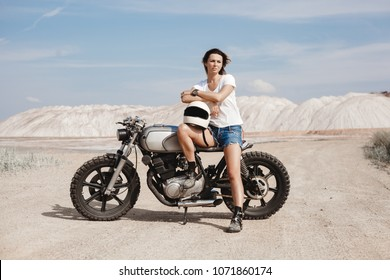Sexy female rider holding helmet and sitting on her custom built cafe racer motorcycle in the desert