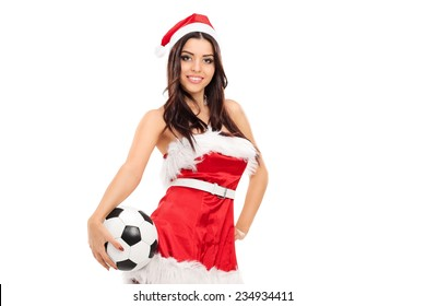 Sexy female in Santa costume holding a football isolated on white background